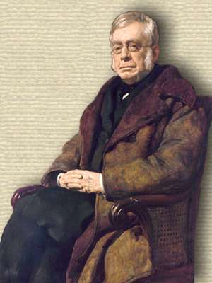 Portrait of Airy wearing wide lapel coat, seated diagonal to left in wooden chair with wicker side, 3/4 body facing forward