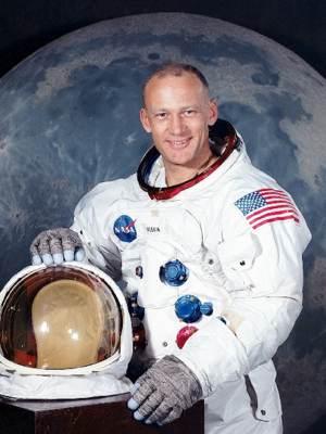 NASA photo of Buzz Aldrin standing in space suit holding helmet - upper body