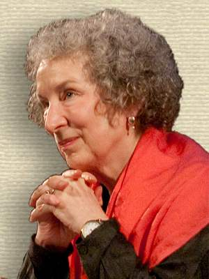 Photo of Margaret Atwood, head and shoulders, facing left, chin resting on clasped hands