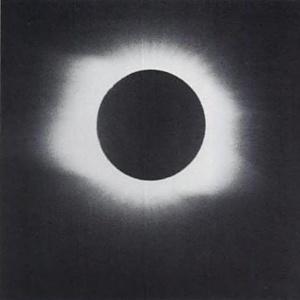 Photograph of total solar eclipse, white wide corona fringe around sun, black circular body of sun, black background.