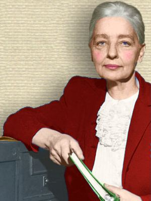 Photo of Ruth Benedict standing leaning on filing cabinet, upper body, facing front, holding ring binder