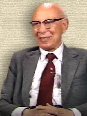 Video still of Bruno Bettelheim, seated for TV interview, upper body facing half-left