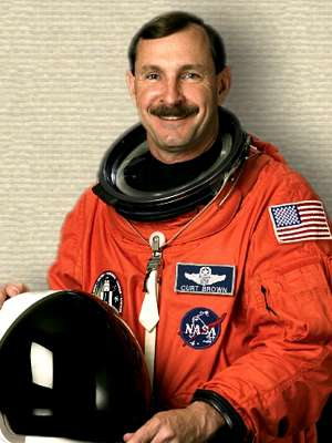 Photo of Curt Brown in space suit, holding space helmet, upper body facing front