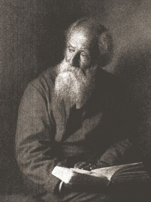 Photo of John Burroughs, upper body, seated with open book in lap, facing left