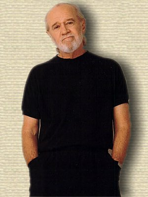 Photo of George Carlin standing, hands in pockets, upper body, facing front