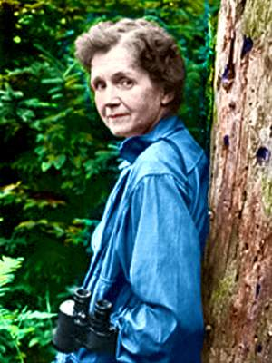 Photo of Rachel Carson, leaning with back on tree, half body, facing forward. Colorization (only) © todayinsci.com