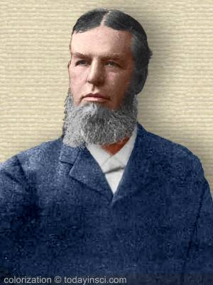 Portrait photo of John W Chadwick with full beard without mustache, upper body, facing slightly left. Colorization © todayinsci
