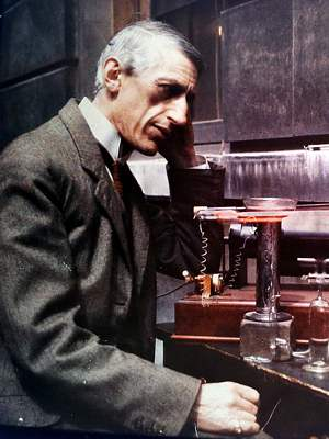 Photo of J Norman Collie upper body facing R, seated at his lab bench observing a red glowing neon tube and associated apparatus