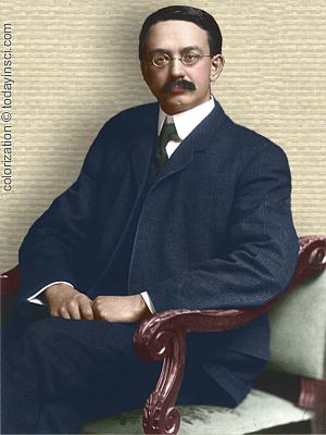 Edwin Grant Conklin photo, upper body, seated in chair, facing forward, colorization © todayinsci