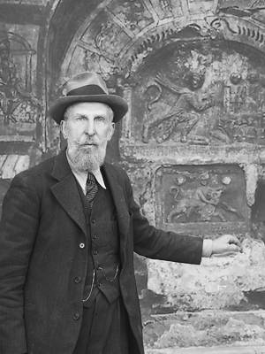 Photo montage of Franz Cumont standing in front of Mithraeum c.1933, upper body, wearing hat, facing front.