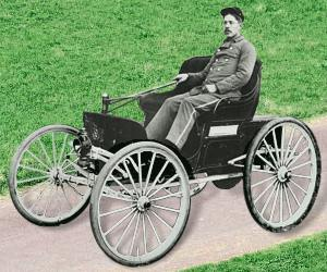 Photo of 1896 Duryea Motor Wagon, with driver. Resembles a horse-drawn open top carriage, cartwheels with spokes (no horse)