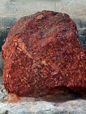 Photo of a red-brown, clay-like boulder of bauxite, part of a commemorative display