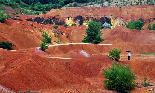 Photo of open-cast bauxite mine, now a museum, at Gánt, Hungary, showing brick-red tailing mounds in front of an excavated cliff