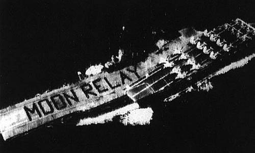 Aerial view of USS Hancock with sailors on flight deck forming the words Moon Relay on the flight deck