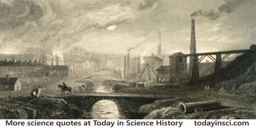 Tall smokestacks and chimneys smoking, industrial brick buildings, stream between, up through center of image, bridge foreground