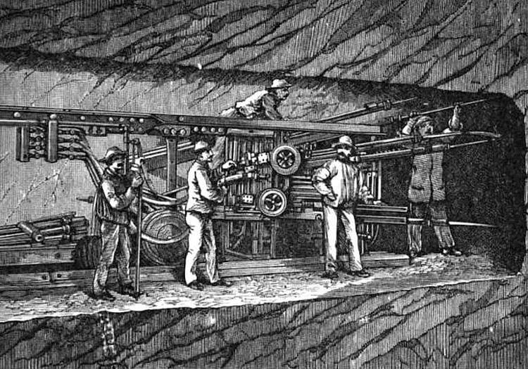 Engraving showing several pneumatic drills mounted on a rail truck, with men operating it to bore into rock face ahead in tunnel