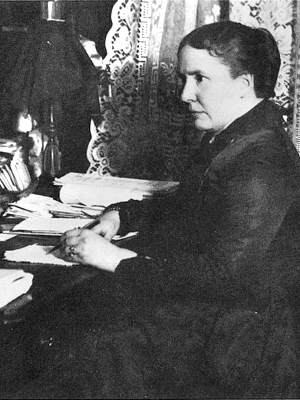 Photo Alice Cunningham Fletcher seated at her writing desk with pen and paperwork, upper body, facing left
