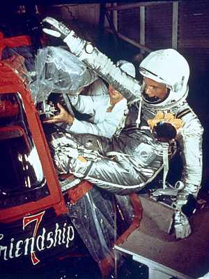 Photo of John Glenn in silver space flight suit entering his capsule feet first through a small hatch. The capsule looks small.