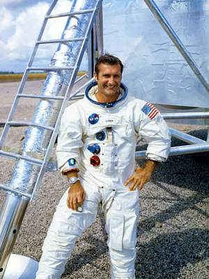 Photo of astronaut Richard Gordon in space suit (no helmet) standing in front of a lunar module (displayed on Earth).