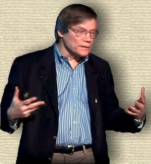 Still from video showing Alan Guth lecturing, upper body, facing right