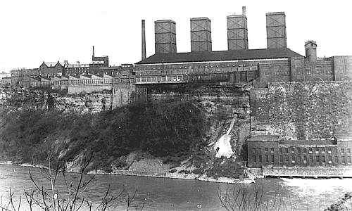 Photo of industrial buildings on top of tall steep cliff above Niagara gorge