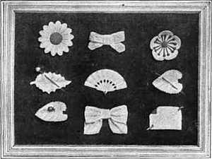 Picture frame with several items of jewelry made of aluminum, including pin-on daisy, buttercup, bow, leaflet, fan, and heart