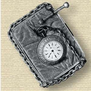 Photo of a watch with ornate bezel on a small cushion around which is wrapped its chain