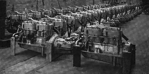 Photo of warehouse with long rows of dozens of automobile engines assembled with crankcase and transmission bell castings