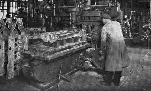 Photo of cast aluminum crank cases in a machine shop. One is on the bed of a milling machine operated by a  worker