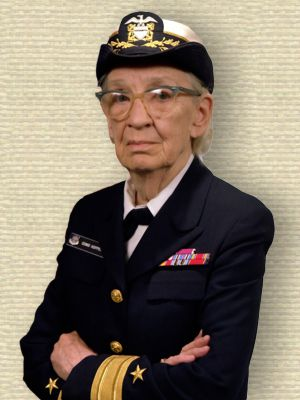 Photo of Rear Admiral Grace Hopper in navy uniform, upper body, arms folded, facing half left