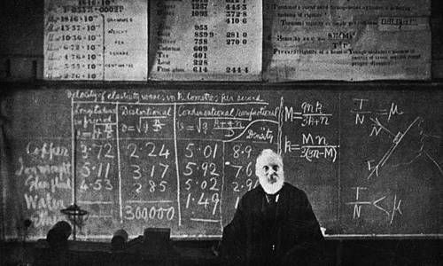 Photo of Lord Kelvin, teaching, standing in front of the chalkboard, at the lecture bench.