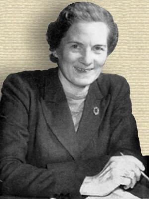 Photo of Margaret K. Knight, seated at desk holding pencil, upper body, facing front