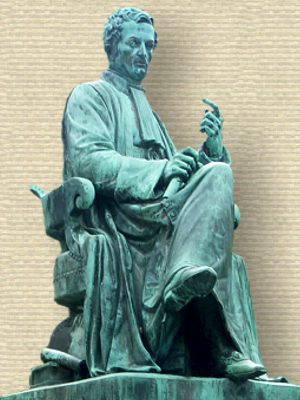 Statue of Rene Laënnec, copper green, seated in gown holding cylinder (stethoscope) in R hand. Another beside chair on book.