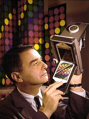 Edwin Land looking right at color Polaroid snapshot and Polaroid camera held above shoulder