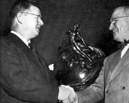 Photo of William Lear shaking hands with President Truman in front of the Collier Trophy - upper body