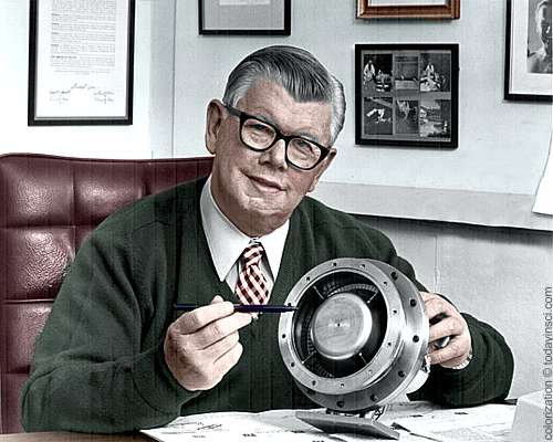 William Lear, seated behind office desk, showing turbine engine - colorization © todayinsci.com - original b/w public domain