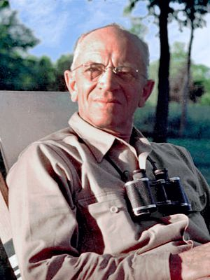 Photo of Aldo Leopold, seated outdoors, upper body, facing front, with binoculars hanging on strap around neck