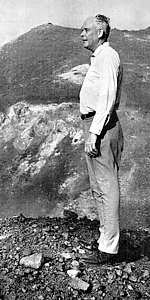 Photo of Charles Lindbergh, age 65, body full length standing on rock-strewn ground with slopes of volcano Krakatau behind him