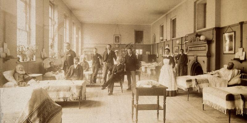 Photo of hospital ward with beds and patients along wall, tended by doctors and nurses, with large windows and fireplace