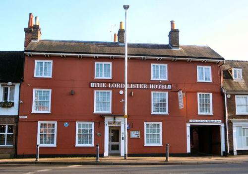 Photo, frontage of Lord Lister Hotel, red brick, three storey building, with pedestrian pavement & street immediately in front.