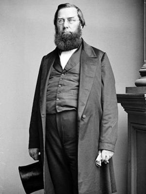 Photo of George Perkins Marsh, older with beard, standing, 3/4 body face front, in frock coat holding top hat by side in R hand
