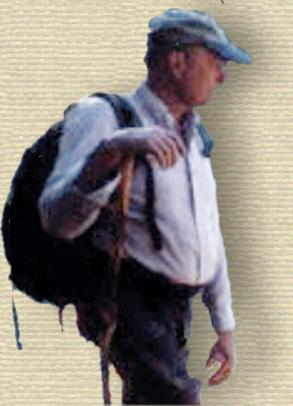 Photo of Chris Maser, 3/4 body facing right, standing resting while hiking, with backpack