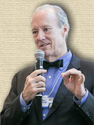 Photo of William McDonough, holding microphone, upper body