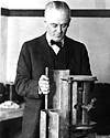 Thumbnail photo of Robert Millikan with his apparatus on bench - upper body