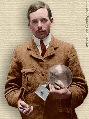 Photo of Henry Moseley, upper body, facing forward, holding glass X-Ray tube. Colorization © todayinsci.com