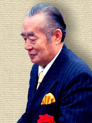 Photo of Yoshiro Nakamats wearing suit, side view, upper body.
