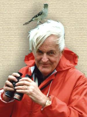 Photo of Roger Tory Peterson with bird on head, wearing red jacket, head and shoulders facing ront, holding binoculars