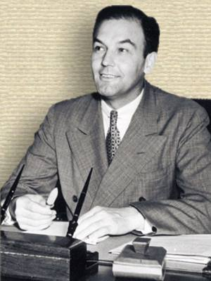 Photo of L. Welch Pogue seated behind and with hands on desk, head and shoulders, facing slightly left