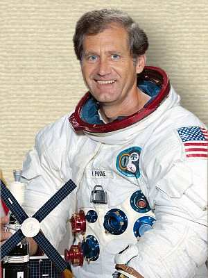 Portrait photo of William Pogue posing in pressure suit, holding Skylab model, upper body, facing forward