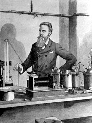 Sketch of Röntgen standing behind lab bench with apparatus including large magnetic coil, capacitors and wires